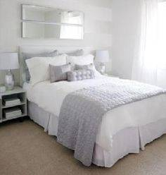 Beautiful bedroom features a gray wingback bed with silver nailhead trim dressed in soft white