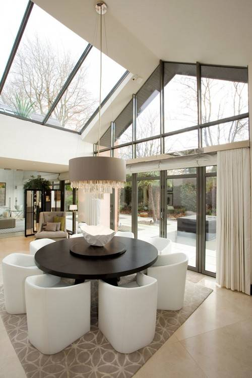 A classic conservatory in white uPVC with open doors displaying a dining  table inside