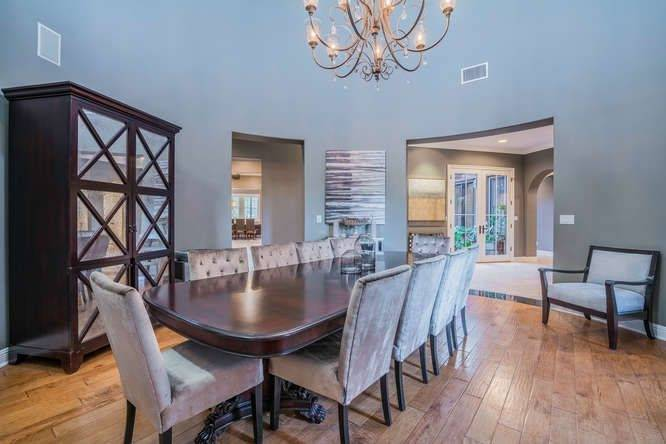 The dining room looks simple with its hardwood flooring and dining set