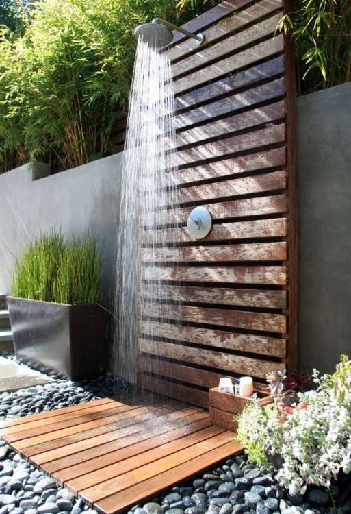 It's a photo of an outdoor shower in a resort hotel near a swimming pool and the sea ocean
