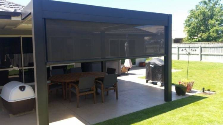 The partially covered outdoor living space boasts a open fire/barbeque