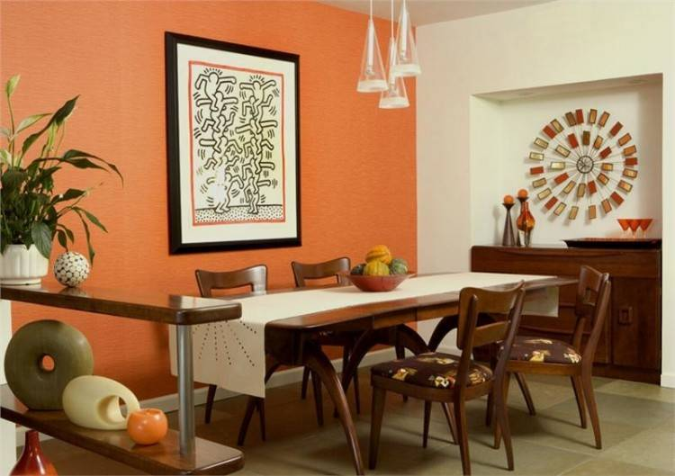 Southwestern orange dining room with chandelier and highback chair