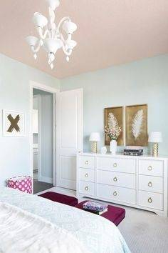 A pink ceiling beautifully complements light blue walls in this stylish  girl's bedroom decorated with white and gold feather art pieces mounted  above a
