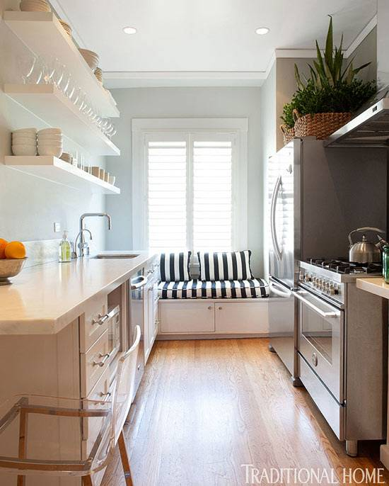 Narrow kitchen in white with a gorgeous island at its heart [Design: Tran +