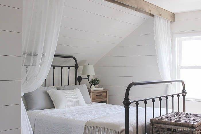 Love a pop of red pillows against the white shiplap bedroom walls and the traditional black wrought iron bed
