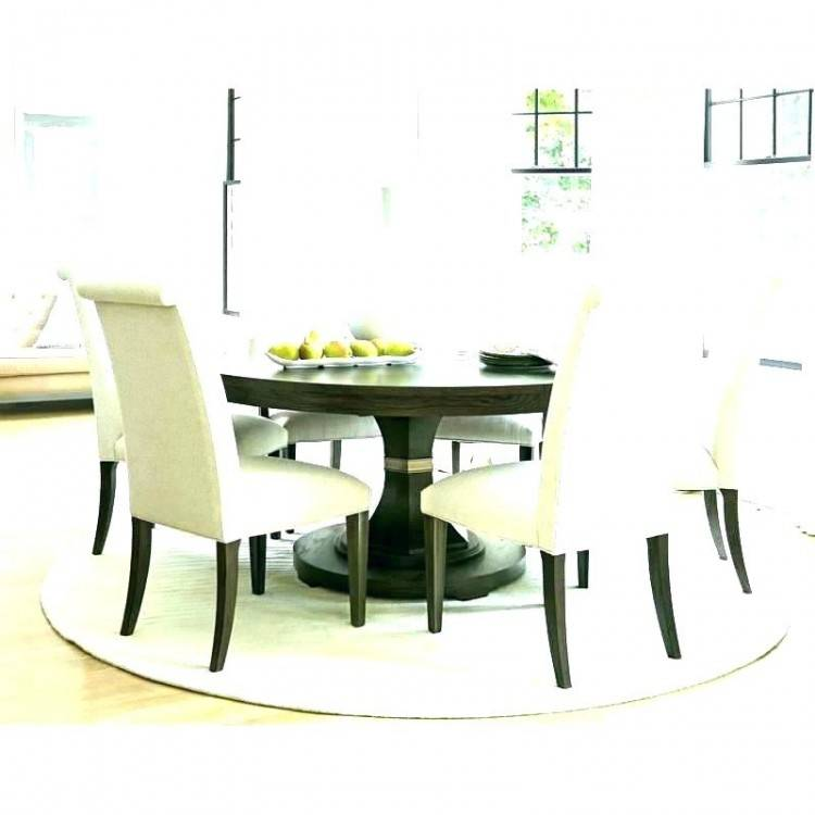 The dining room boasts an oval dining set with classy seats lighted by a chandelier