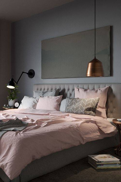 The walls  and floor are grey and there's a huge floor lamp set above the bed