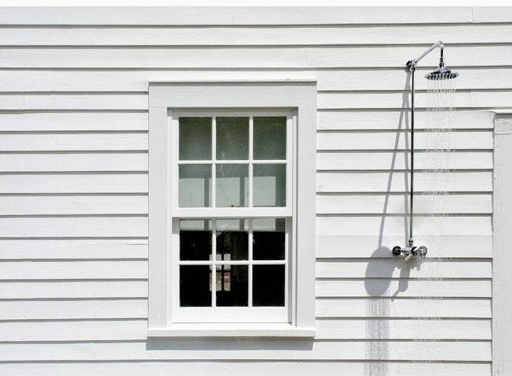 A pool house in the Berkshires in Massachusetts has an outdoor shower sided with white clapboard