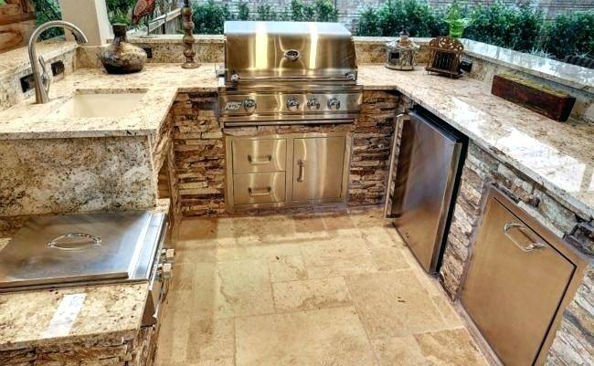 Amazing kitchen features white cabinets paired with Taj Mahal Quartzite  countertops and a white subway tiled backsplash